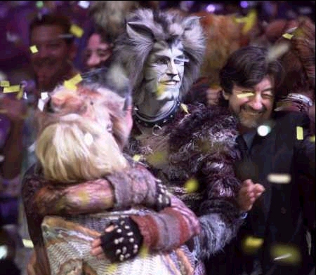 Gillian Lynne hugging Jennyanydots (Sharon Wheatley) with Munkustrap (Jeffry Denman) and Trevor Nunn in the background.